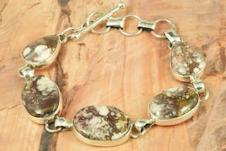 "Beautiful Sterling Silver Bracelet featuring Five Genuine Wild Horse Stones. This stone is also known as ""Crazy Horse"". It is mined near Globe, Arizona. Created by Navajo Artist Tony Garcia. Signed by the artist."