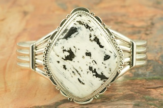 Stunning Bracelet featuring Genuine White Buffalo Turquoise set in heavy gauge Sterling Silver. This Beautiful Stone is formed from the minerals Calcite and Iron. It is mined near Tonopah Nevada. Created by Navajo Artist John Nelson. Signed by the artist.