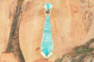 Beautiful Pendant featuring Genuine Sleeping Beauty Turquoise inlaid between ribbons of Sterling Silver. Free 18&quot; Sterling Silver Chain with Purchase of Pendant. Designed by Navajo Artist Calvin Begay. Signed by the artist.