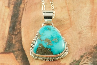 Genuine Castle Dome Turquoise set in Sterling Silver Pendant. Created by Navajo Artist Kathy Yazzie. Signed by the artist. The Castle Dome Turquoise Mine is located about 30 miles from the Sleeping Beauty Mine, near Globe, Arizona. The Castle Dome Mine has not been in operation since the early 1970s. Free 18 inch Sterling Silver Chain with purchase of pendant.