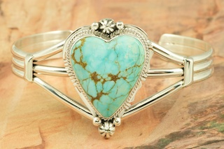 Stunning Heart Bracelet featuring Genuine Number 8 Turquoise set in heavy gauge Sterling Silver. The Number 8 mine is located in Eureka County Nevada. Since 1976 there has been no Number 8 Turquoise mined. There is however, an existing stock pile that Mr. Dowell Ward, the last owner of the Number 8 mine, had stocked away for later sorting. The Turquoise is a collector's item--because once the reserve is gone there will be no more material released onto the market. The Gold Mining Company owns the claim to the Number 8 mine and it has been swallowed up by the gold mining operations. This is some of the last Number 8 Turquoise to be had and will be a great addition to your collection. Created by Navajo Artist Lucy Valencia. Signed L. J. by the artist.