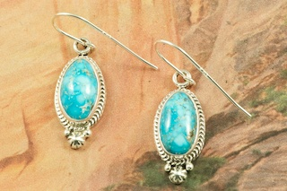 Genuine High Grade Kingman Web Turquoise set in Sterling Silver Earrings. Created by Navajo Artist Lucy Valencia. Signed L. J. by the artist. The Mineral Park Mine, in the Cerbat Mountains 14 miles northwest of Kingman, was first mined by Indians centuries before white man came to the area. It is one of the three sites of prehistoric mining localities in the state of Arizona. Mineral Park was the most extensively worked area by the Indians of the three. S.A. �Chuck� Colbaugh found a cache of stone hammers uncovered in ancient trenches and tunnels, when he had the turquoise mining concession in May of 1962. Ithaca Peak and Turquoise Mine (formally called Aztec Mountain or Aztec Peak) are the most famous of the peaks in the area containing turquoise.