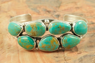 7 Beautiful Genuine Manassa Turquoise Stones set in Sterling Silver Bracelet. This Turquoise is also referred to as King�s Manassa Turquoise. The Manassa Turquoise mine is located in Manassa, Conejos County, Colorado. Created by Navajo Artist Evelyn Yazzie. Signed by the artist.
