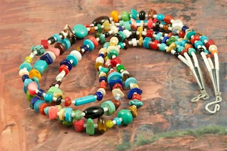 Beautiful 3 strand Treasure Necklace featuring Genuine Turquoise, Spiny Oyster Shell, Coral, Freshwater Pearls, Jasper and Melon Shell Heishi.  Sterling Silver Cones and Clasp.  Created by Santo Domingo Artist Carol Pacheco. The Santo Domingo Pueblo is in New Mexico, near Santa Fe. 