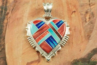 Beautiful Heart Pendant featuring Genuine Sleeping Beauty Turquoise, Spiny Oyster Shell and Blue Lapis inlaid between ribbons of Sterling Silver. Pretty Fire and Ice Lab Opal Accents. Free 18&quot; Sterling Silver Chain with Purchase of Pendant. Created by Navajo Artist Rick Tolino. Signed by the artist.