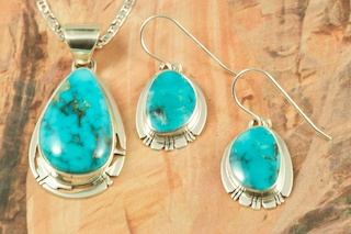 Stunning Pendant and Earrings Set featuring Genuine High Grade Candelaria Turquoise set in Sterling Silver.  Created by Navajo Artist Phillip Sanchez. Signed by the artist. Free 18 inch Sterling Silver Chain. Candelaria Turquoise comes from the large Candelaria Silver and Gold mine in Nevada in an area not to far from Tonopah. It is currently closed with no mining activity and as such Candelaria turquoise is rare and considered a collectable. The turquoise in this area was usually found in thin veins and is known for its beautiful almost electric blue stones, sometimes with a light matrix. Over the last few years Candelaria turquoise has been seen again in today�s turquoise market from older collections with beautiful dark blue stones with a beautiful matrix pattern and has now been cut and is appearing in fine jewelry. This mine produces some of the most unusual and beautiful patterns, no two stones are ever alike.