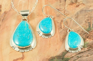 Stunning Pendant and Earrings Set featuring Genuine High Grade Kingman Turquoise set in Sterling Silver. Created by Navajo Artist Phillip Sanchez. Signed by the artist. Free 18 inch Sterling Silver Chain. The Mineral Park Mine, in the Cerbat Mountains 14 miles northwest of Kingman, was first mined by Indians centuries before white man came to the area. It is one of the three sites of prehistoric mining localities in the state of Arizona. Mineral Park was the most extensively worked area by the Indians of the three. S.A. �Chuck� Colbaugh found a cache of stone hammers uncovered in ancient trenches and tunnels, when he had the turquoise mining concession in May of 1962. Ithaca Peak and Turquoise Mine (formally called Aztec Mountain or Aztec Peak) are the most famous of the peaks in the area containing turquoise.