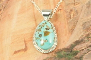 Genuine Candelaria Turquoise set in Sterling Silver Pendant. Created by Navajo Artist Tony Garcia. Signed by the artist. Free 18 inch Sterling Silver Chain with purchase of pendant. Candelaria Turquoise comes from the large Candelaria Silver and Gold mine in Nevada in an area not to far from Tonopah. It is currently closed with no mining activity and as such Candelaria turquoise is rare and considered a collectable. The turquoise in this area was usually found in thin veins and is known for its beautiful almost electric blue stones, sometimes with a light matrix. Over the last few years Candelaria turquoise has been seen again in today�s turquoise market from older collections with beautiful dark blue stones with a beautiful matrix pattern and has now been cut and is appearing in fine jewelry. This mine produces some of the most unusual and beautiful patterns, no two stones are ever alike.
