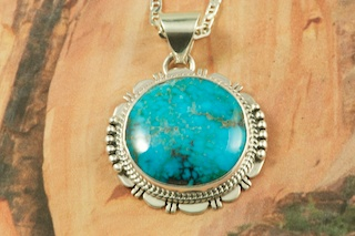 "Genuine Apache Blue Turquoise set in Sterling Silver Pendant. Free 18"" Sterling Silver Chain with purchase. Created by Navajo Artist John Nelson. Signed by the artist. The Apache Blue Mine turquoise mine, is a small mine with lots of potential. The mine is located near Tonopah, Nevada in the Candelaria Mountain range. In recent years the mine, (an open pit) has re-opened rendering Apache Blue turquoise with beautiful blue stones with eye popping black matrix. This high quality Apache turquoise is very rare and hard to find, even in this mine, but it's what every turquoise miner is searching for. Unfortunately only a small amount of this nice natural hard turquoise with really beautiful dark blue, webbed nuggets have been discovered. This turquoise is truly some of the nicest from Nevada."