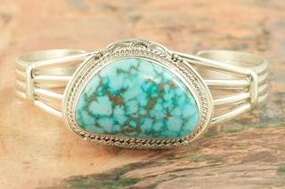 Genuine High Grade Kingman Web Turquoise set in Sterling Silver Bracelet. Created by Navajo Artist John Nelson. Signed by the artist. The Mineral Park Mine, in the Cerbat Mountains 14 miles northwest of Kingman, was first mined by Indians centuries before white man came to the area. It is one of the three sites of prehistoric mining localities in the state of Arizona. Mineral Park was the most extensively worked area by the Indians of the three. S.A. �Chuck� Colbaugh found a cache of stone hammers uncovered in ancient trenches and tunnels, when he had the turquoise mining concession in May of 1962. Ithaca Peak and Turquoise Mine (formally called Aztec Mountain or Aztec Peak) are the most famous of the peaks in the area containing turquoise.