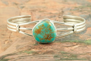 Genuine Manassa Turquoise set in Sterling Silver Bracelet. This Turquoise is also referred to as King�s Manassa Turquoise. The Manassa Turquoise mine is located in Manassa, Conejos County, Colorado. Created by Navajo Artist Lucy Valencia. Signed L. J. by the artist.