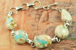 Mother Nature is Amazing! The beautiful pattern in the stone (called the matrix) is all natural. Genuine Boulder Turquoise set in Sterling Silver Bracelet. The cabochon is Boulder Turquoise, you can see the veins of Turquoise running through the host rock. The Boulder Turquoise Mine is located in northeast Nevada. It was discovered in 1970 by a Shoshone sheep herder. Production is small due to the remote location and winter weather. Boulder Turquoise is valued for both it's beauty and rarity. Every stone is unique. Created by Navajo Artist Tony Garcia. Signed by the artist.