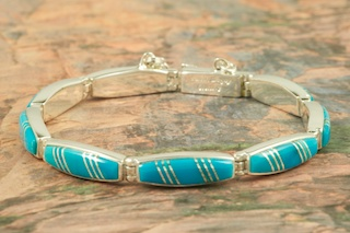 Genuine High Grade Sleeping Beauty Turquoise inlaid between ribbons of Sterling Silver. Stunning Bracelet Designed by Navajo Artist Calvin Begay. Signed by the artist.