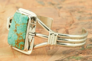 Genuine Number 8 Mine Turquoise set in Heavy Gauge Sterling Silver Bracelet. Created by Navajo Artist Phillip Sanchez. Signed by the artist.  The Number 8 mine is located in Eureka County Nevada. Since 1976 there has been no Number 8 Turquoise mined. There is however, an existing stock pile that Mr. Dowell Ward, the last owner of the Number 8 mine, had stocked away for later sorting. The Turquoise is a collector's item--because once the reserve is gone there will be no more material released onto the market. The Gold Mining Company owns the claim to the Number 8 mine and it has been swallowed up by the gold mining operations. This is some of the last Number 8 Turquoise to be had and will be a great addition to your collection.