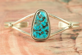 Sterling Silver Bracelet featuring a Genuine Sleeping Beauty Turquoise Stone. The Sleeping Beauty Turquoise mine is located in Gila County, Arizona. The mine is now closed and the stones are obtained from private collections. Created by Navajo Artist Victor Chavez. Signed by the artist.