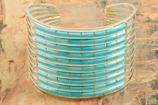 Stunning Bracelet featuring Genuine Sleeping Beauty Turquoise inlaid between ribbons of Sterling Silver. The Sleeping Beauty Turquoise mine is located in Gila County, Arizona. Created by Zuni Artists Anson and Letitica Wallace. Signed by the artists. The Zuni Pueblo is located in New Mexico, Land of Enchantment.