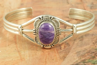 Stunning Bracelet featuring Genuine Charoite set Sterling Silver. Created by Navajo Artist Evelyn Yazzie. Signed by the artist. Charoite is a Beautiful and interesting gemstone first introduced in the US around 1976. It's vivid colors range from lavender to deep chatoyant purple. It is mined in Siberia Russia near Charo River, Lake Baikal region. High grade charoite is distinguished by mixtures of deep rich purple and silky zones, in swirly and/or needle-like chatoyant patterns/sprays.