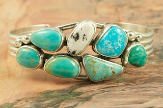 Stunning Sterling Silver Bracelet featuring Genuine Candelaria Turquoise, Turquoise Mountain Turquoise, 3 King's Manassa Turquoise Stones, Apache Blue Turquoise and White Buffalo Turquoise. Created by Navajo Artist Evelyn Yazzie. Signed by the artist.