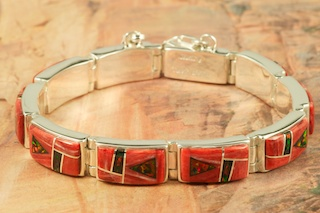 Stunning Bracelet featuring Genuine Spiny Oyster Shell and Black Jade inlaid between ribbons of Sterling Silver. Fire and Ice Lab Opal Accents. Designed by Navajo Artist Calvin Begay. Signed by the artist.