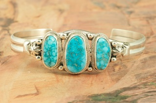 Genuine High Grade Kingman Turquoise Stones set in Sterling Silver Bracelet. Created by Navajo Artist Lucy Valencia. Signed L. J. by the artist. The Mineral Park Mine, in the Cerbat Mountains 14 miles northwest of Kingman, was first mined by Indians centuries before white man came to the area. It is one of the three sites of prehistoric mining localities in the state of Arizona. Mineral Park was the most extensively worked area by the Indians of the three. S.A. �Chuck� Colbaugh found a cache of stone hammers uncovered in ancient trenches and tunnels, when he had the turquoise mining concession in May of 1962. Ithaca Peak and Turquoise Mine (formally called Aztec Mountain or Aztec Peak) are the most famous of the peaks in the area containing turquoise.