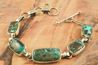 Genuine Candelaria Turquoise set in Sterling Silver Bracelet. Created by Navajo Artist Tony Garcia. Signed by the artist. Candelaria Turquoise comes from the large Candelaria Silver and Gold mine in Nevada in an area not to far from Tonopah. It is currently closed with no mining activity and as such Candelaria turquoise is rare and considered a collectable. The turquoise in this area was usually found in thin veins and is known for its beautiful almost electric blue stones, sometimes with a light matrix. Over the last few years Candelaria turquoise has been seen again in today�s turquoise market from older collections with beautiful dark blue stones with a beautiful matrix pattern and has now been cut and is appearing in fine jewelry. This mine produces some of the most unusual and beautiful patterns, no two stones are ever alike.