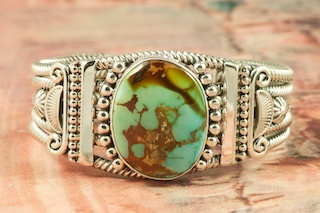 The Silver Design on this Bracelet is Amazing! Heavy gauge Sterling Silver Bracelet featuring Genuine Royston Turquoise. The Royston Turquoise Mine was originally known as the Royal Blue Mine. It produces Turquoise that has a mixture of blues and greens in the same formation. The Royston Turquoise Mine is located in Nye County, Nevada. Created by Navajo Master Silversmith Aaron Toadlena. Signed by the artist.