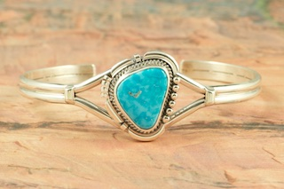 Genuine High Grade Kingman Web Turquoise set in Sterling Silver Bracelet. Created by Navajo Artist Evelyn Yazzie. Signed by the artist. The Mineral Park Mine, in the Cerbat Mountains 14 miles northwest of Kingman, was first mined by Indians centuries before white man came to the area. It is one of the three sites of prehistoric mining localities in the state of Arizona. Mineral Park was the most extensively worked area by the Indians of the three. S.A. �Chuck� Colbaugh found a cache of stone hammers uncovered in ancient trenches and tunnels, when he had the turquoise mining concession in May of 1962. Ithaca Peak and Turquoise Mine (formally called Aztec Mountain or Aztec Peak) are the most famous of the peaks in the area containing turquoise.