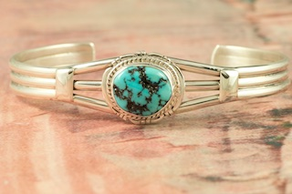 Beautiful Sterling Silver Bracelet featuring Genuine Sleeping Beauty Turquoise. The Sleeping Beauty Turquoise mine is located in Gila County, Arizona. The mine is now closed and the stones are obtained from private collections. Created by Navajo Artist Lucy Valencia. Signed L. J. by the artist.