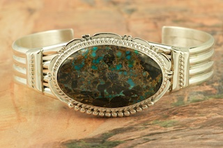 Beautiful Sterling Silver Bracelet featuring Genuine Sunnyside Turquoise. The matrix on this rare stone is outstanding. The Sunnyside mine is located in northern Nevada near the town of Tuscarora in the Tuscarora mountain range. The mine is no longer in operation as it has become part of a gold mining operation and a privately owned ranch. The Sunnyside mine was mined mostly in the 70's. You won't find much of this great turquoise around anymore except for old stashes. Created by Navajo Artist John Nelson. Signed by the artist.