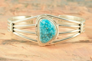 Genuine High Grade Kingman Web Turquoise set in Sterling Silver Bracelet. Created by Navajo Artist Kathy Yazzie. Signed by the artist. The Mineral Park Mine, in the Cerbat Mountains 14 miles northwest of Kingman, was first mined by Indians centuries before white man came to the area. It is one of the three sites of prehistoric mining localities in the state of Arizona. Mineral Park was the most extensively worked area by the Indians of the three. S.A. �Chuck� Colbaugh found a cache of stone hammers uncovered in ancient trenches and tunnels, when he had the turquoise mining concession in May of 1962. Ithaca Peak and Turquoise Mine (formally called Aztec Mountain or Aztec Peak) are the most famous of the peaks in the area containing turquoise.