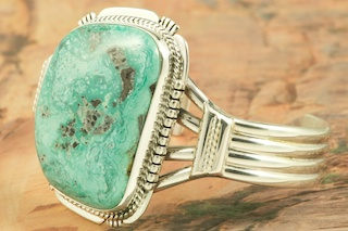 Genuine Blue Diamond Turquoise Stone set in Heavy Gauge Sterling Silver Bracelet. The Blue Diamond mine, located in central Nevada, opened in the late 1950�s and was mined up to 1980. This mine is considered a �hat mine� of which there are very few. A hat mine is a small deposit of turquoise that, �you can cover with your hat.� This mine is now closed and buried under thousands of tons of rock. It is now obtained from private collections. Created by Navajo Artist John Nelson. Signed by the artist.