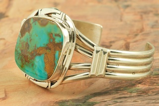 Genuine Royston Turquoise set in Heavy Gauge Sterling Silver Bracelet. The Royston Turquoise Mine was originally known as the Royal Blue Mine. It produces Turquoise that has a mixture of blues and greens in the same formation. The Royston Turquoise Mine is located in Nye County, Nevada. Created by Navajo Artist Phillip Sanchez. Signed by the artist.