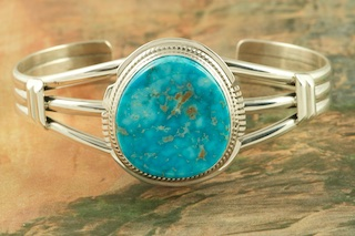 "Amazing Matrix (the pattern in the stone) in this Genuine High Grade Kingman Turquoise set in Sterling Silver Bracelet. Created by Navajo Artist Larson Lee. Signed by the artist. The Mineral Park Mine, in the Cerbat Mountains 14 miles northwest of Kingman, was first mined by Indians centuries before white man came to the area. It is one of the three sites of prehistoric mining localities in the state of Arizona. Mineral Park was the most extensively worked area by the Indians of the three. S.A. ""Chuck"" Colbaugh found a cache of stone hammers uncovered in ancient trenches and tunnels, when he had the turquoise mining concession in May of 1962. Ithaca Peak and Turquoise Mine (formally called Aztec Mountain or Aztec Peak) are the most famous of the peaks in the area containing turquoise."