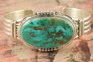 "Genuine Turquoise Mountain Mine Turquoise set in Sterling Silver Bracelet. Created by Navajo Artist John Nelson. Signed by the artist. The Turquoise Mountain Mine is located in the Mineral Park Mining District, Mohave County, Arizona. Although Turquoise Mountain is located near the Kingman Turquoise Mine it is considered a classic mine in its own right because the Turquoise is so different in appearance. It is also known as ""Old Man Turquoise""."