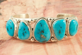5 Genuine Sleeping Beauty Turquoise Stones set in Heavy Gauge Sterling Silver Bracelet. The Sleeping Beauty Turquoise mine is located in Gila County, Arizona. The Sleeping Beauty Turquoise mine is now closed. The stones are obtained from private collections. Created by Navajo Artist Joe Piaso. Signed by the artist.