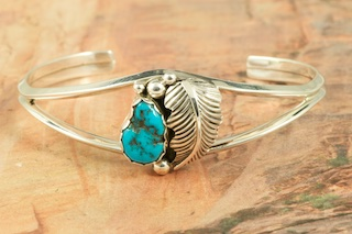 Genuine Sleeping Beauty Turquoise set in Sterling Silver Bracelet. The beautiful Sterling Silver Feather represents life. The Sleeping Beauty Turquoise mine is located in Gila County, Arizona. The mine is now closed and the stones are obtained from private collections. Navajo jewelry signed A. S. by the artist.
