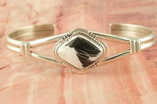 Genuine White Buffalo Turquoise set in Sterling Silver Bracelet. This Beautiful Stone is formed from the minerals Calcite and Iron. It is mined near Tonopah Nevada. Created by Navajo Artist Larson Lee. Signed by the artist.
