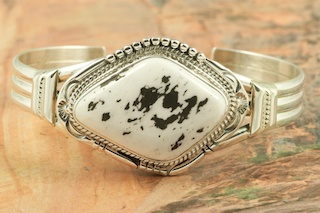 Genuine White Buffalo Turquoise set in Sterling Silver Bracelet. This Beautiful Stone is formed from the minerals Calcite and Iron. It is mined near Tonopah Nevada. Created by Navajo Artist John Nelson. Signed by the artist.