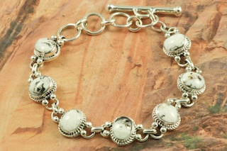 7 Beautiful White Buffalo Turquoise Sones set in  Sterling Silver. This Beautiful Stone is formed from the minerals Calcite and Iron. It is mined near Tonopah Nevada. Bracelet Created by Navajo Artist Lucy Valencia. Signed by the artist.