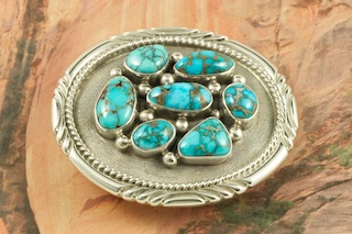 Genuine Candelaria Turquoise set in Sterling Silver Belt Buckle. Created by Navajo Artist Lyle Piaso. Signed by the artist. Candelaria Turquoise comes from the large Candelaria Silver and Gold mine in Nevada in an area not to far from Tonopah. It is currently closed with no mining activity and as such Candelaria turquoise is rare and considered a collectable. The turquoise in this area was usually found in thin veins and is known for its beautiful almost electric blue stones, sometimes with a light matrix. Over the last few years Candelaria turquoise has been seen again in todays turquoise market from older collections with beautiful dark blue stones with a beautiful matrix pattern and has now been cut and is appearing in fine jewelry. This mine produces some of the most unusual and beautiful patterns, no two stones are ever alike.