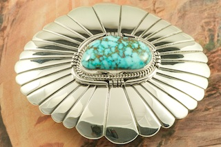 Genuine High Grade Kingman Web Turquoise set in Sterling Silver Belt Buckle. Created by Navajo Artist John Nelson. Signed by the artist. The Mineral Park Mine, in the Cerbat Mountains 14 miles northwest of Kingman, was first mined by Indians centuries before white man came to the area. It is one of the three sites of prehistoric mining localities in the state of Arizona. Mineral Park was the most extensively worked area by the Indians of the three. S.A. �Chuck� Colbaugh found a cache of stone hammers uncovered in ancient trenches and tunnels, when he had the turquoise mining concession in May of 1962. Ithaca Peak and Turquoise Mine (formally called Aztec Mountain or Aztec Peak) are the most famous of the peaks in the area containing turquoise.