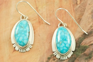 Genuine High Grade Kingman Web Turquoise set in Sterling Silver Earrings. Created by Navajo Artist Phillip Sanchez. Signed by the artist. The Mineral Park Mine, in the Cerbat Mountains 14 miles northwest of Kingman, was first mined by Indians centuries before white man came to the area. It is one of the three sites of prehistoric mining localities in the state of Arizona. Mineral Park was the most extensively worked area by the Indians of the three. S.A. �Chuck� Colbaugh found a cache of stone hammers uncovered in ancient trenches and tunnels, when he had the turquoise mining concession in May of 1962. Ithaca Peak and Turquoise Mine (formally called Aztec Mountain or Aztec Peak) are the most famous of the peaks in the area containing turquoise.
