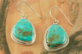 "Genuine Turquoise Mountain Mine Turquoise set in Sterling Silver French Wire Earrings. The Turquoise Mountain Mine is located in the Mineral Park Mining District, Mohave County, Arizona. Although Turquoise Mountain is located near the Kingman Turquoise Mine it is considered a classic mine in its own right because the Turquoise is so different in appearance. It is also known as ""Old Man Turquoise"". Created by Navajo Artist Lucy Valencia. Signed L. J. by the artist."
