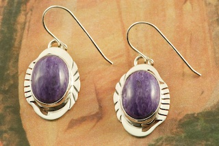 Genuine Charoite set in Sterling Silver French Wire Earrings. Created by Navajo Artist Herbert Pino. Signed by the artist. Charoite is a Beautiful and interesting gemstone first introduced in the US around 1976. It's vivid colors range from lavender to deep chatoyant purple. It is mined in Siberia Russia near Charo River, Lake Baikal region. High grade charoite is distinguished by mixtures of deep rich purple and silky zones, in swirly and/or needle-like chatoyant patterns/sprays.