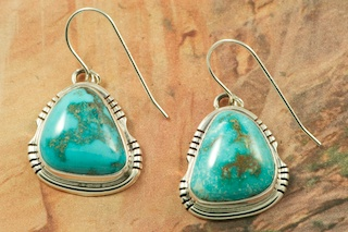 Genuine Sunnyside Turquoise set in Sterling Silver French Wire Earrings. The matrix on this rare stone is outstanding. The Sunnyside mine is located in northern Nevada near the town of Tuscarora in the Tuscarora mountain range. The mine is no longer in operation as it has become part of a gold mining operation and a privately owned ranch. The Sunnyside mine was mined mostly in the 70's. You won't find much of this great turquoise around anymore except for old stashes. Created by Navajo Artist Arkie Nelson. Signed by the artist.