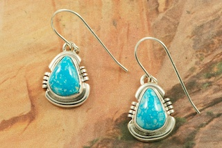 Genuine High Grade Kingman Web Turquoise set in Sterling Silver Earrings. Created by Navajo Artist Arkie Nelson. Signed by the artist. The Mineral Park Mine, in the Cerbat Mountains 14 miles northwest of Kingman, was first mined by Indians centuries before white man came to the area. It is one of the three sites of prehistoric mining localities in the state of Arizona. Mineral Park was the most extensively worked area by the Indians of the three. S.A. �Chuck� Colbaugh found a cache of stone hammers uncovered in ancient trenches and tunnels, when he had the turquoise mining concession in May of 1962. Ithaca Peak and Turquoise Mine (formally called Aztec Mountain or Aztec Peak) are the most famous of the peaks in the area containing turquoise.