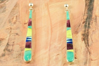 Beautiful Long Dangle Earrings featuring Genuine Turquoise, Spiny Oyster Shell, Gaspeite and Blue Lapis inlaid between ribbons of Sterling Silver. Fire and Ice Lab Opals Accents. Post Earrings Designed by Navajo Artist Calvin Begay. Signed by the artist.