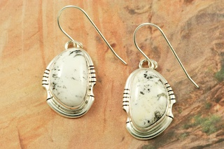 Genuine White Buffalo Turquoise set in Sterling Silver French Wire Earrings. This Beautiful Stone is formed from the minerals Calcite and Iron. It is mined near Tonopah Nevada. Created by Navajo Artist Arkie Nelson. Signed by the artist.