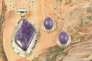"Pendant and Earrings Set featuring Charoite set in Sterling Silver. Charoite is a Beautiful and interesting gemstone first introduced in the US around 1976. It's vivid colors range from lavender to deep chatoyant purple. It is mined in Siberia Russia near Charo River, Lake Baikal region. High grade charoite is distinguished by mixtures of deep rich purple and silky zones, in swirly and/or needle-like chatoyant patterns/sprays. Free 18"" Sterling Silver Chain with Purchase of Pendant. Created by Navajo Artists Bennie Ration and Evelyn Yazzie. Signed by the artist."