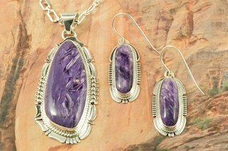 "Pendant and Earrings Set featuring Charoite set in Sterling Silver. Charoite is a Beautiful and interesting gemstone first introduced in the US around 1976. It's vivid colors range from lavender to deep chatoyant purple. It is mined in Siberia Russia near Charo River, Lake Baikal region. High grade charoite is distinguished by mixtures of deep rich purple and silky zones, in swirly and/or needle-like chatoyant patterns/sprays. Free 18"" Sterling Silver Chain with Purchase of Pendant. Created by Navajo Artists Bennie Ration and Kathy Yazzie. Signed by the artist."